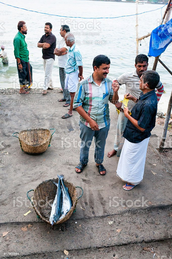 Men bartering for fish along the shore in Kochi, India stock photo
