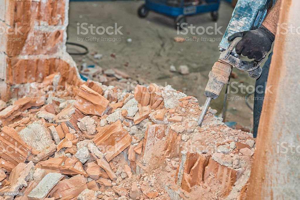 Men breaking wall using a jackhammer stock photo
