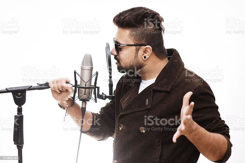 Men brown coat and glasses singing into a condenser microphone stock photo