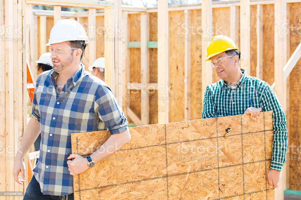 Men carry plywood through construction site stock photo