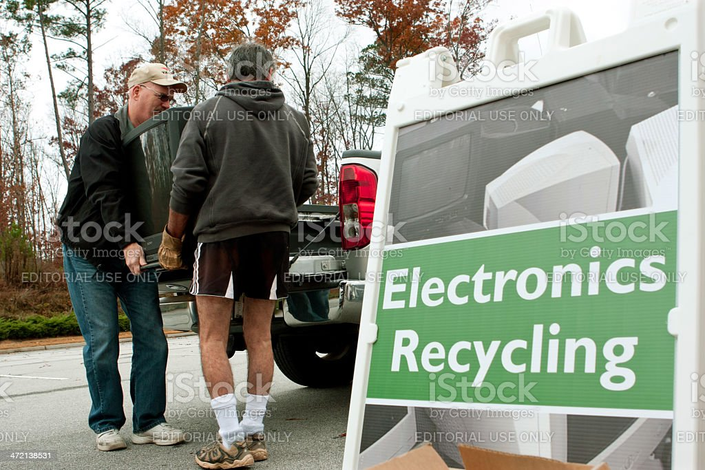 Men Carry TV To Drop Off At Recycling Event stock photo