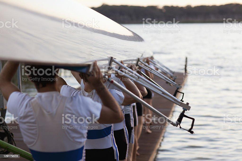 Men carrying long canoe over hear stock photo