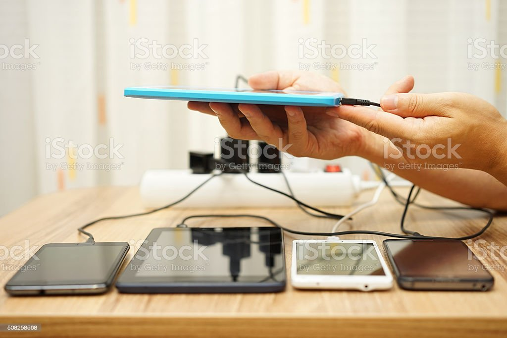 Men connected charger to tablet computer after four digital devices stock photo