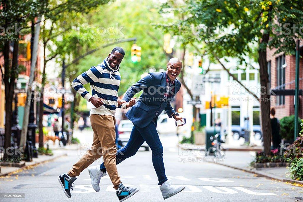 Men couple crossing the street New York City stock photo