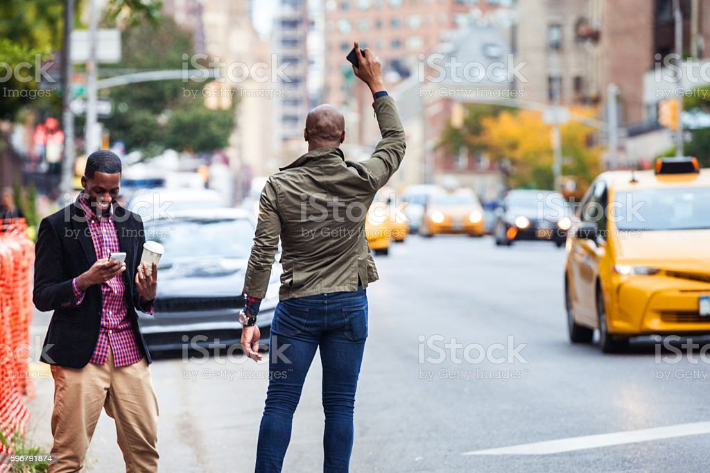 Men couple hailing a taxi in New York stock photo