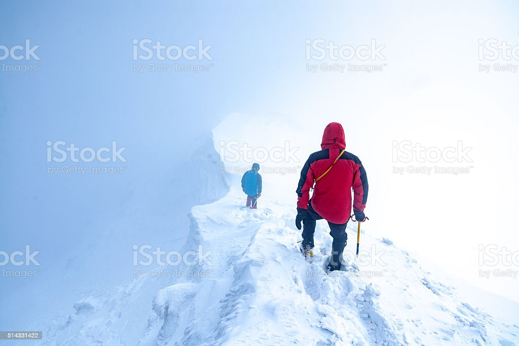 2 men descending a glacier peak into the clouds stock photo