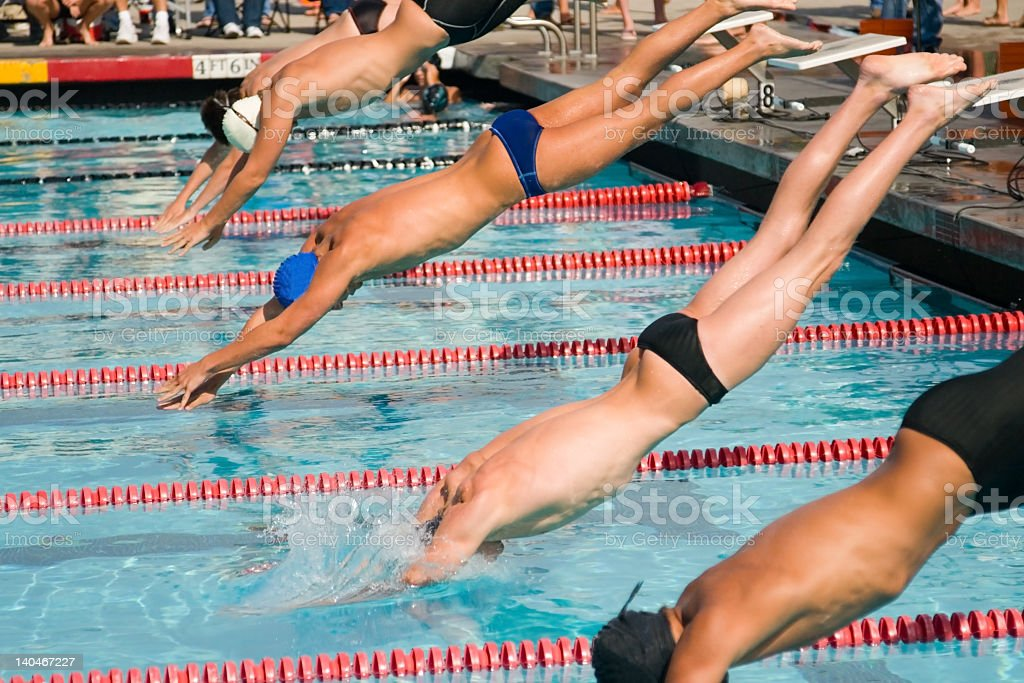 Men diving into the pool for swimming finals stock photo