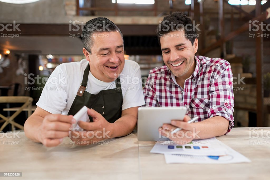 Men doing the books at a restaurant stock photo