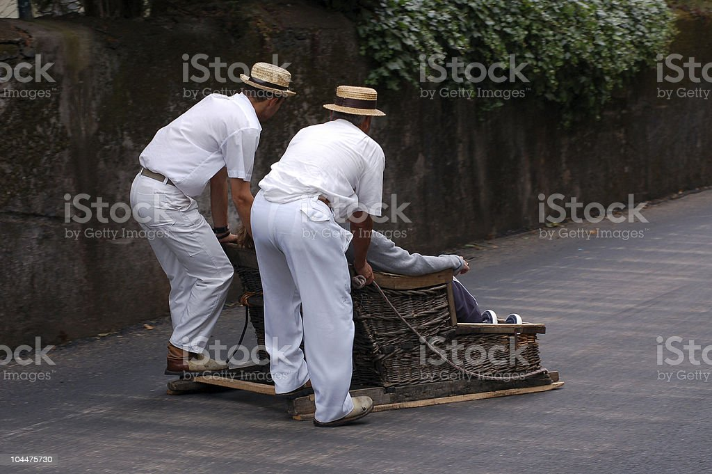 2 men dressed in white pushing another man on a sledge stock photo