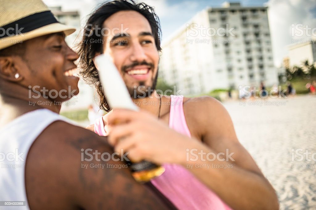 men drinking beers at the party beach in Miami stock photo