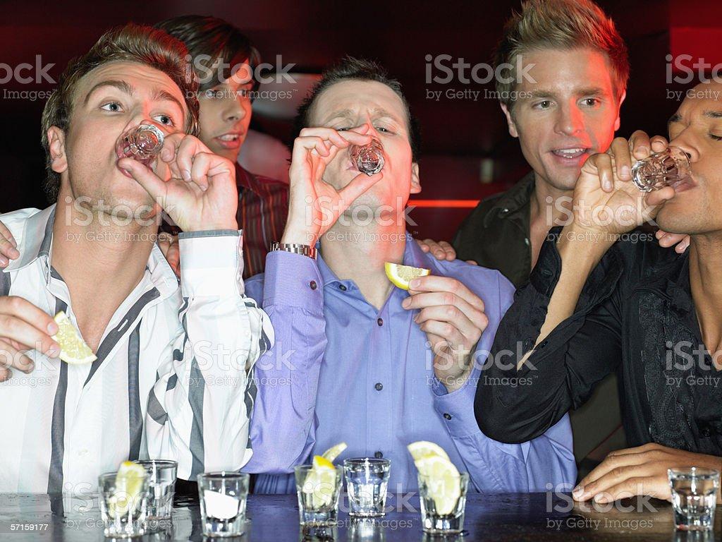 Men drinking shots at a bar stock photo