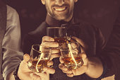 Men drinking whiskey, close up of glasses and hands