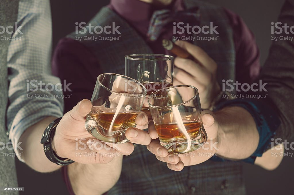 Men drinking whiskey, close up of glasses and hands stock photo