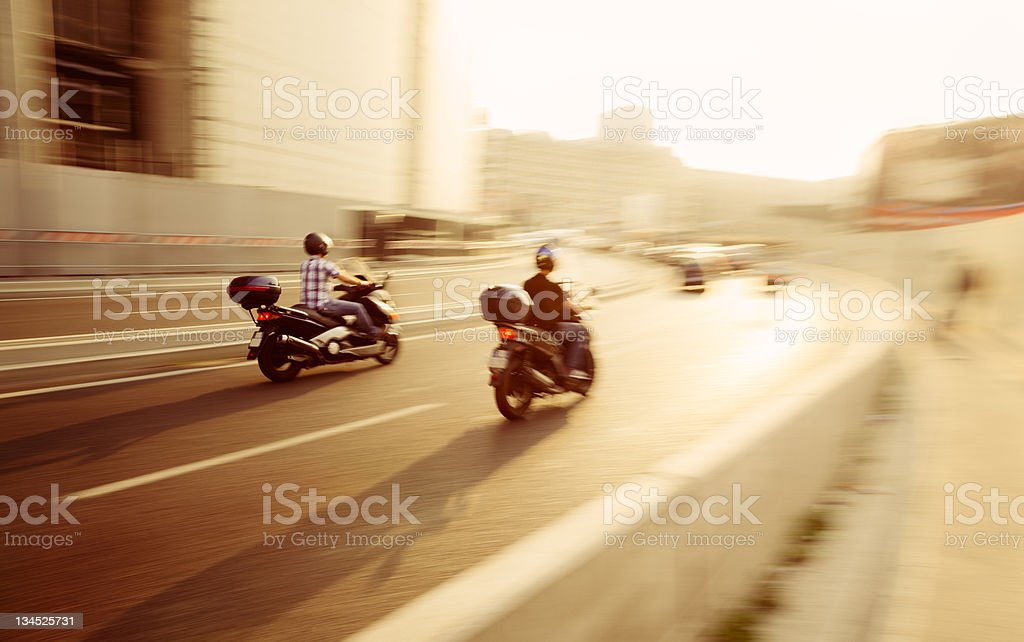 Men Drive Fast Scooters on Milan 's Streets stock photo
