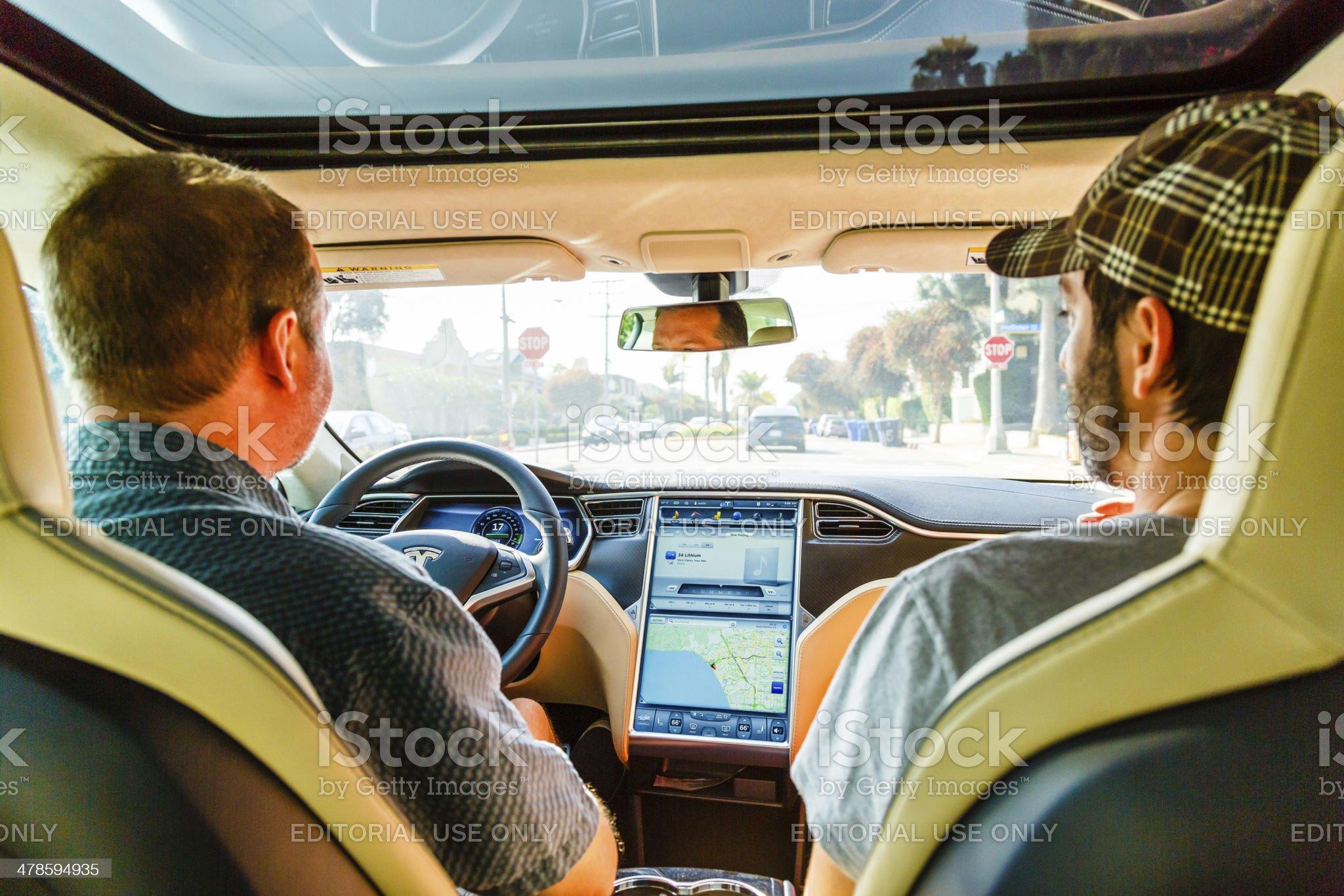 Men driving in Tesla Model S car royalty-free stock photo