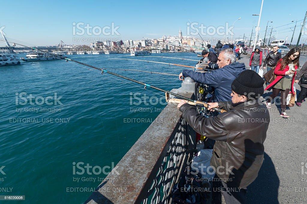 Men fishing on Galata Bridge in Istanbul stock photo