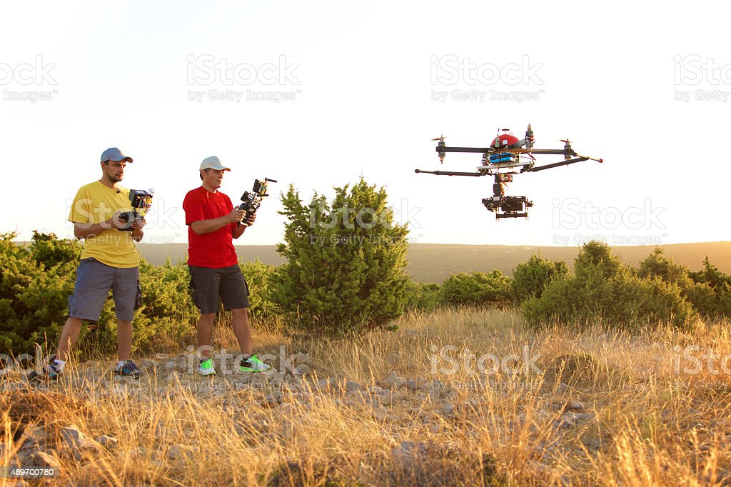 Men flying drone at sunset stock photo