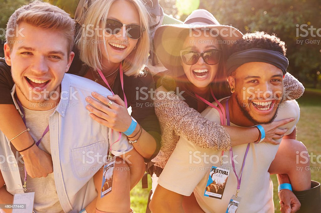 Men Giving Woman Piggybacks On Their Way To Music Festival stock photo