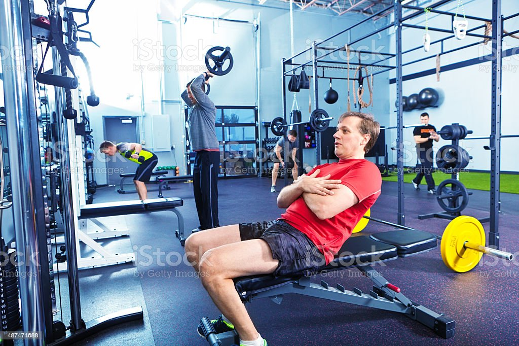 Men Group and Coach Weight Lifting Training in Health Club stock photo