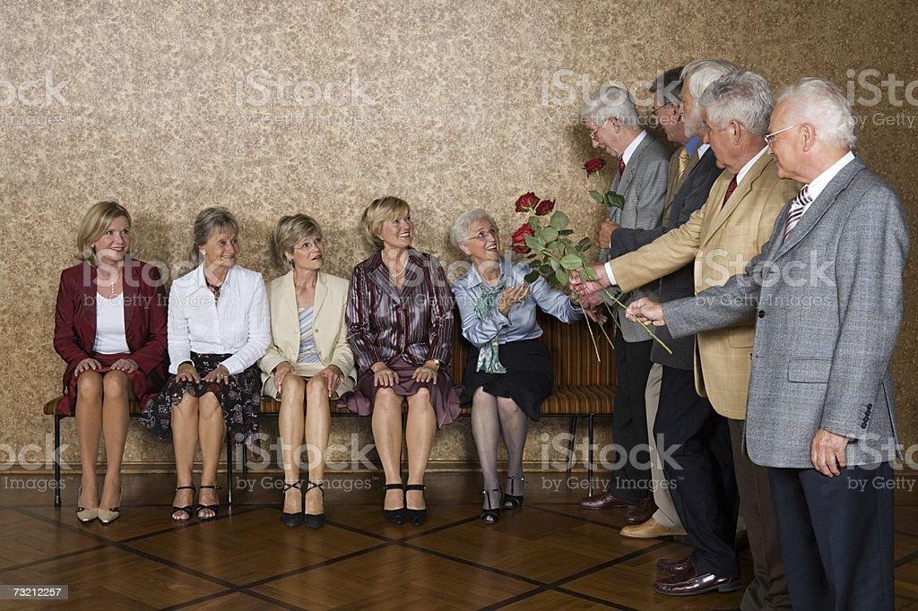 Men handing roses to one senior woman stock photo