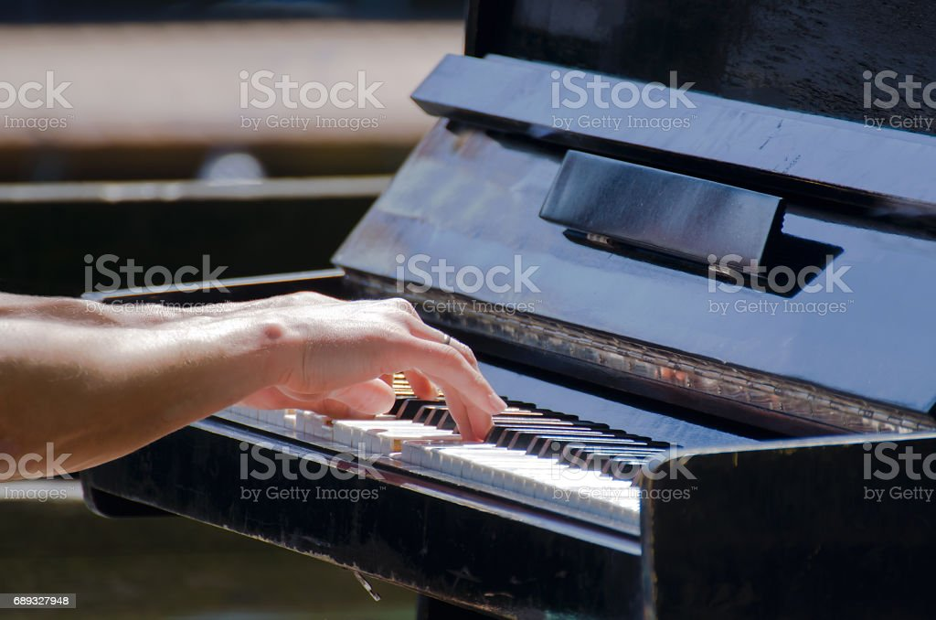 Men hands touching old piano keys stock photo