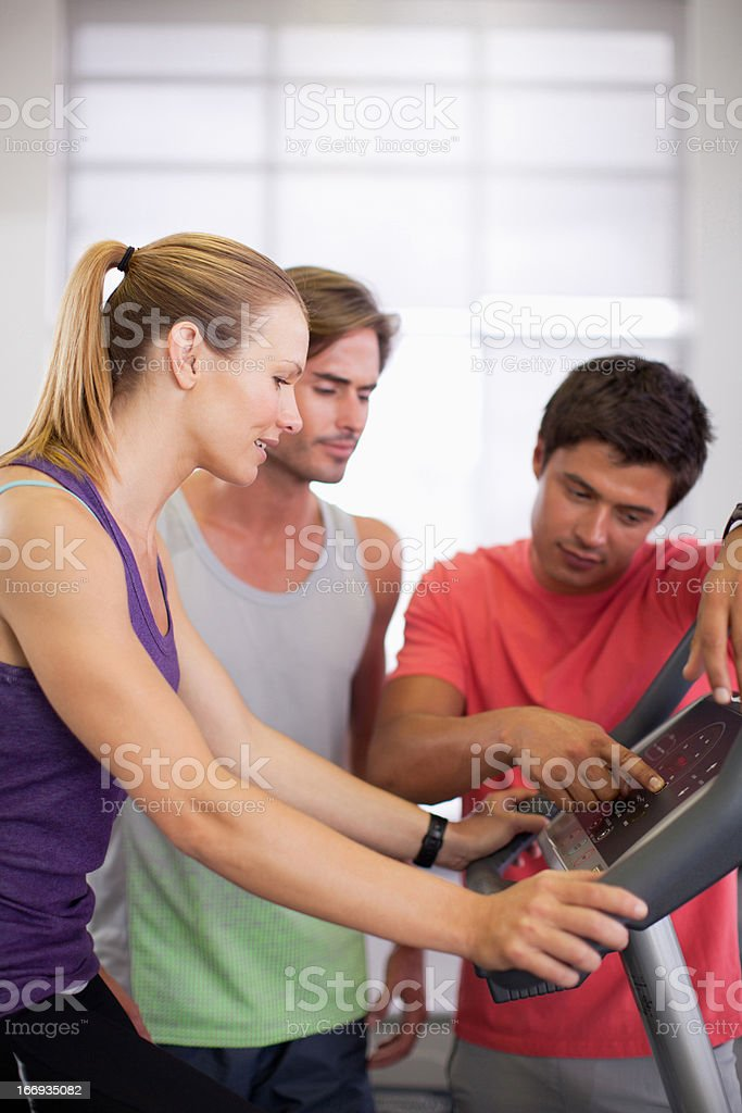 Men helping woman with treadmill in gymnasium stock photo