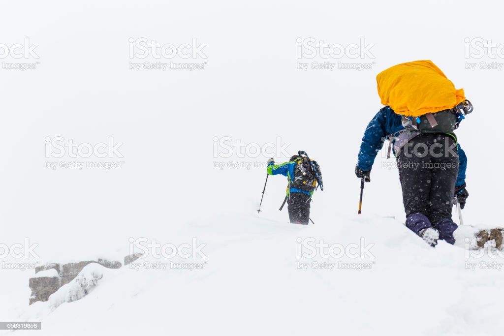 Men hiking on mountain during snow storm stock photo