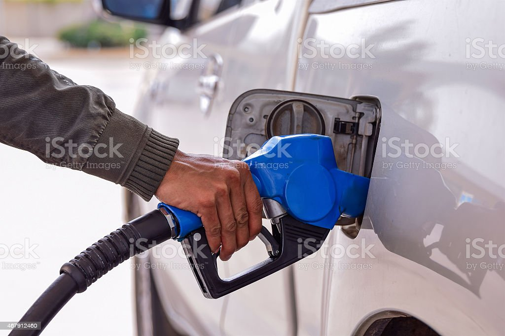 Men hold Fuel nozzle to add fuel in car stock photo