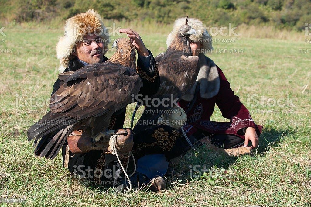 Men hold golden eagles, Almaty, Kazakhstan. stock photo
