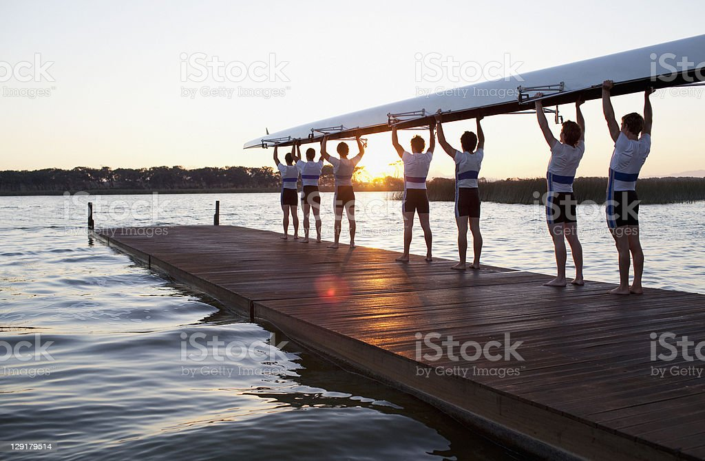 Men holding canoe over heads stock photo