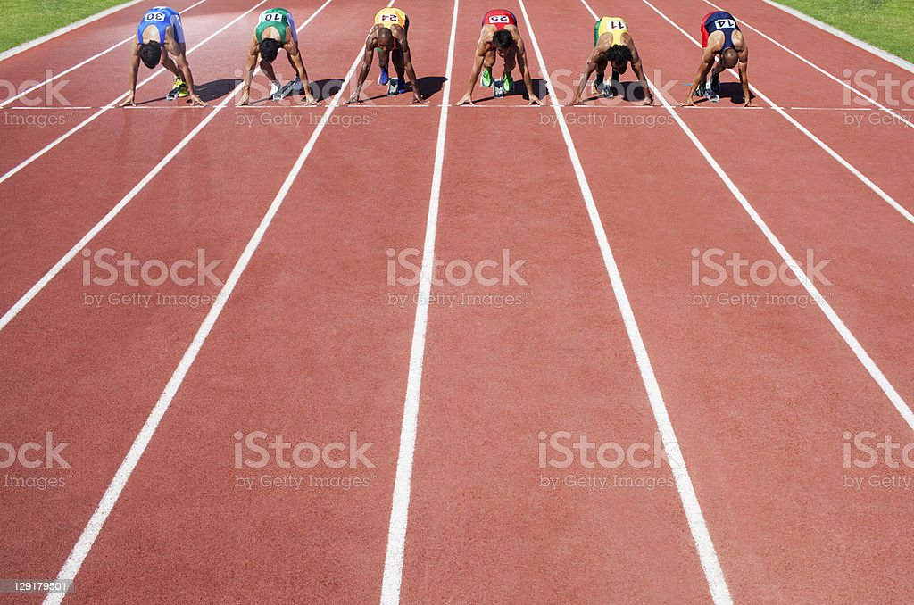 Men in a start block on an athletic track royalty-free stock photo