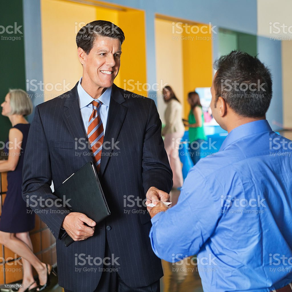 Men in corporate attire shaking hands royalty-free stock photo