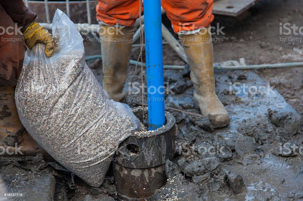 Men in orange overalls and boots work on a borehole stock photo