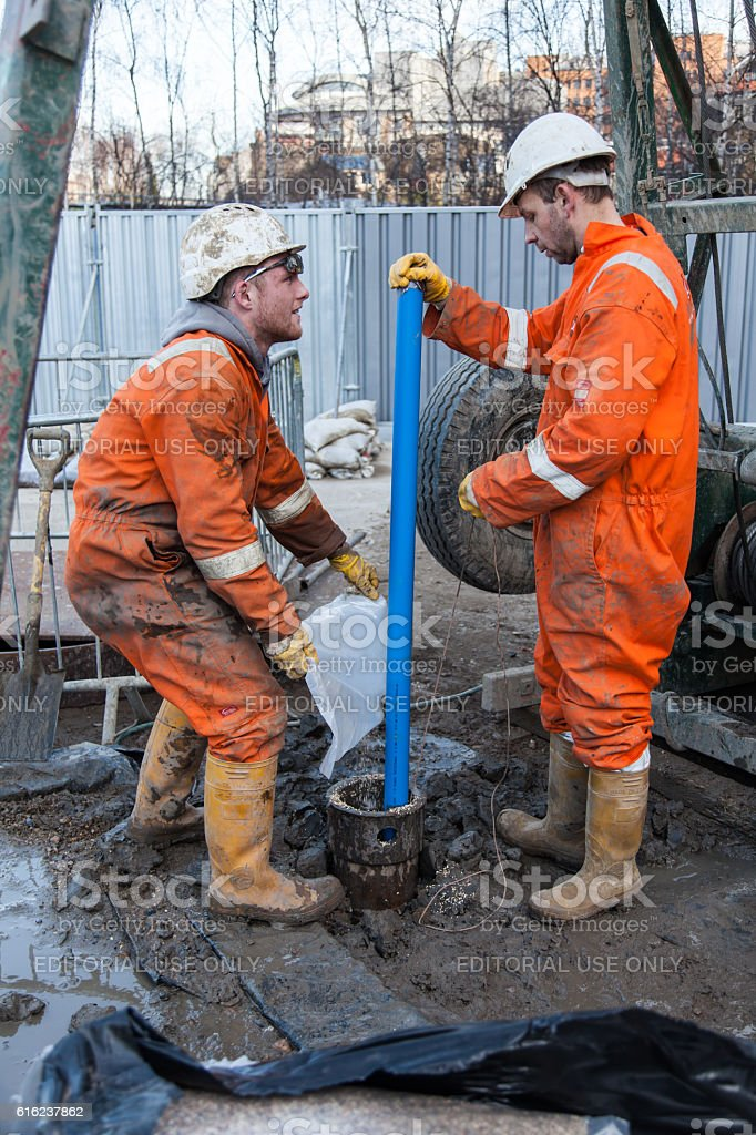 Men in orange overalls hard hat work on a borehole stock photo