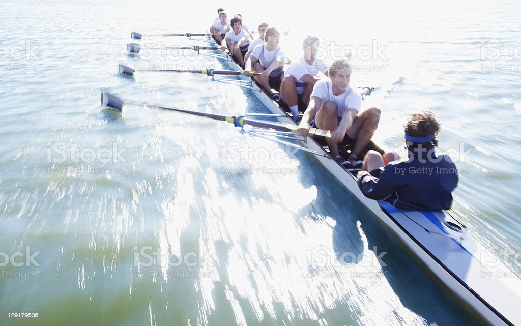 Men in row boat oaring stock photo