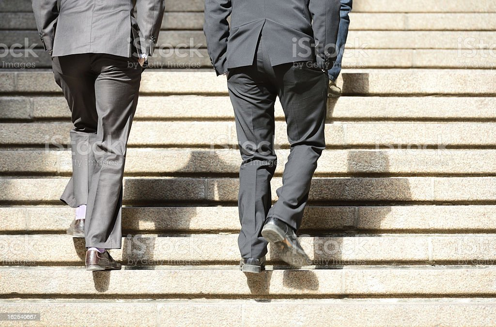 Men in suits taking the step up royalty-free stock photo
