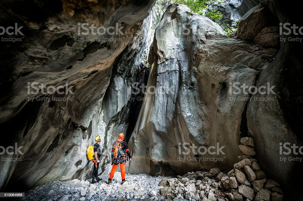 Men in the cave looking at huge rock cliff stock photo