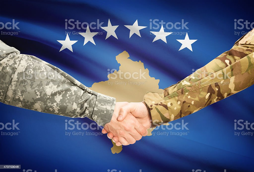 Men in uniform shaking hands with flag - Kosovo stock photo