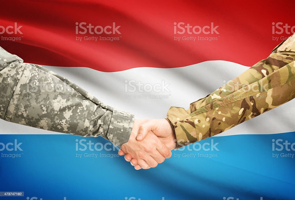 Men in uniform shaking hands with flag - Luxembourg stock photo