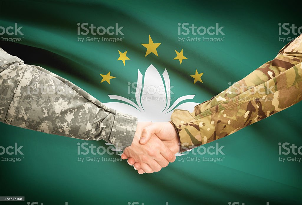 Men in uniform shaking hands with flag - Macau stock photo