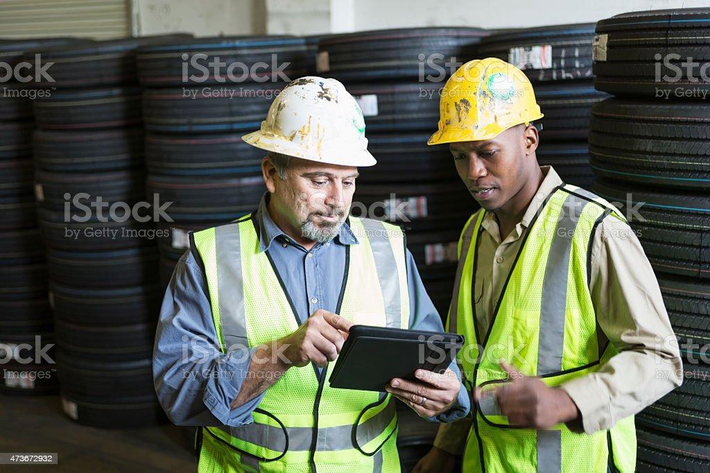 Men in warehouse using digital tablet stock photo