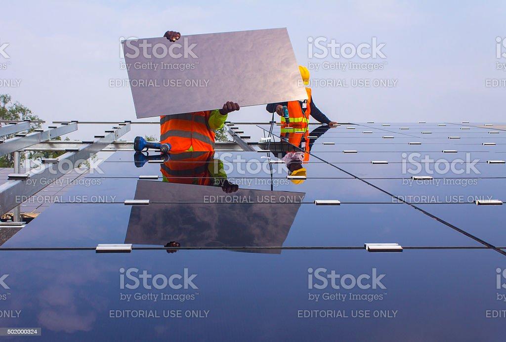 Men installing solar panels stock photo
