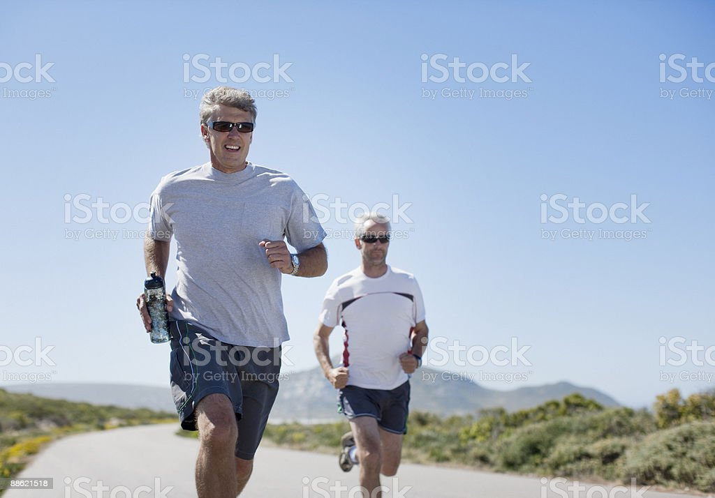 Men jogging and carrying water bottles stock photo