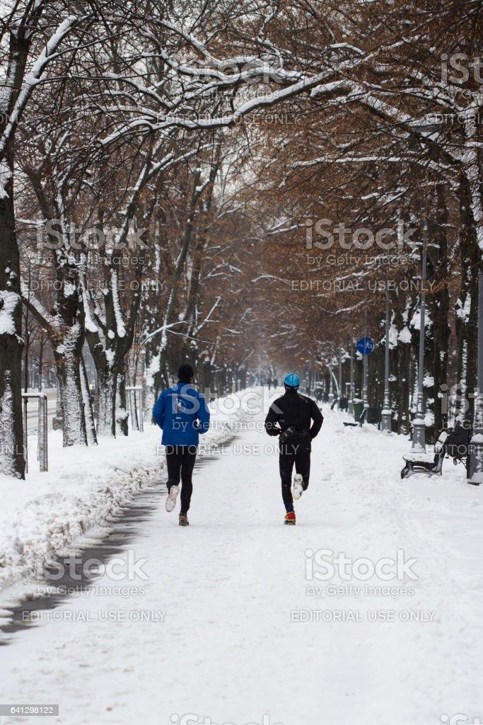 Men jogging in the park in winter time stock photo