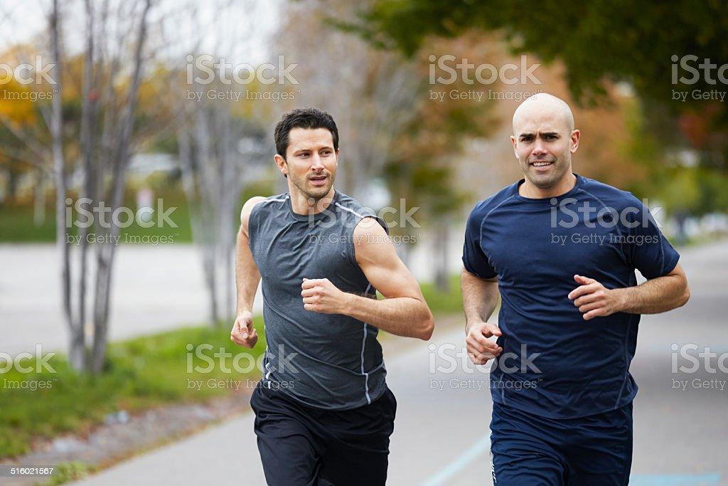 Men jogging on footpath in autumn city stock photo