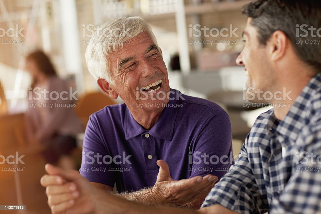 Men laughing together in cafe stock photo