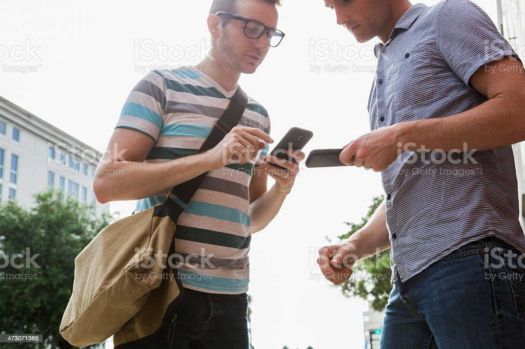Men looking at mobile phones stock photo
