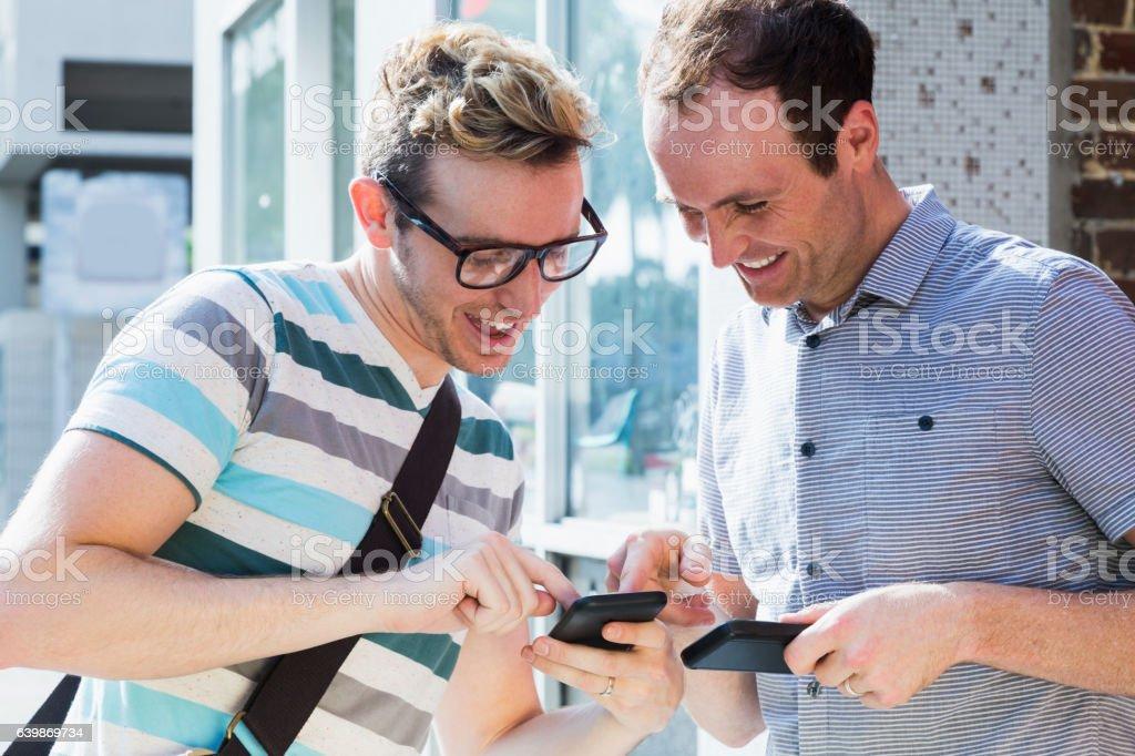 Two men using mobile phones.