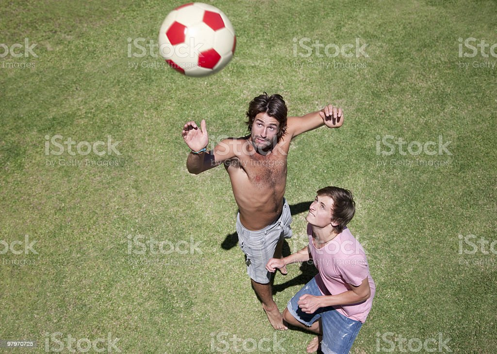 Men on grass jumping for ball royalty-free stock photo