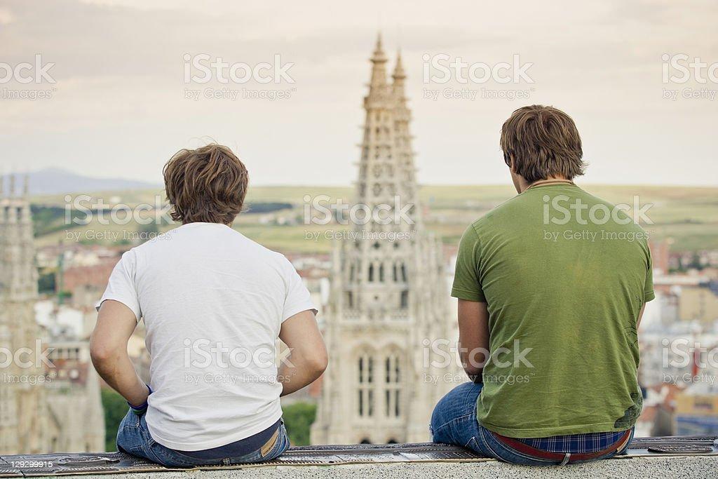 Men on wall overlooking urban cityscape stock photo